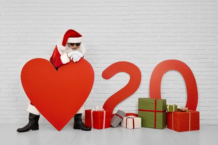 Smiling Saint Nicholas in red costume, white gloves and black sunglasses lean on big red paper heart with background of white wall. Concept of New 2020 Year