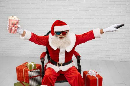 Authentic Saint Nicholas with emotional facial expression sitting in comfortable armchair with TV zapper and striped bucket of pop corn. Senior man in 3d glasses looking at camera and posing in studio
