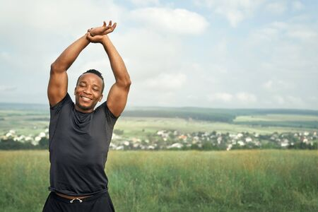 Active, muscular athlete in black t shirt and black shorts doing exercises for hands. Handsome sportsman raising hand up. Smiling man posing on nature, looking at camera.