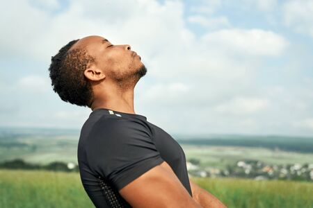 Close up of handsome, sportive african man training and meditating. Sportsman wearing in black t shirt doing yoga. Muscular athlete posing outdoors with closed eyes. 스톡 콘텐츠