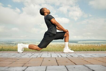 Muscular athlete wearing in black t shirt, shorts and white socks, sneakers, posing outdoors side view. Handsome man doing exercises with stretching for feet in morning.