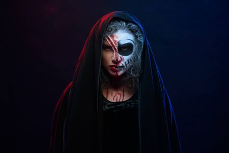 Attractive young woman in halloween costume with creative idea of skeleton makeup posing in studio with dark background. Concept of tradition, celebration and culture