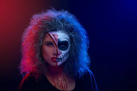 Portrait of young beautiful girl with curly grey hair and makeup skeleton on her face over background of red and blue light. Concept of horror, halloween and tradition Foto de archivo