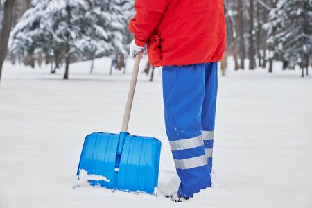 Cropped view of male janitor in process of working in winter in park. Man in blue uniform and red jacket removing snow from sidewalks with shovel. Concept of maintenance and service.