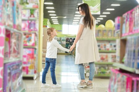 Young mother and little, pretty daughter standing and holding hands in big shopping centre together. Family shopping in department store with beautiful children toys. Foto de archivo - 132072321