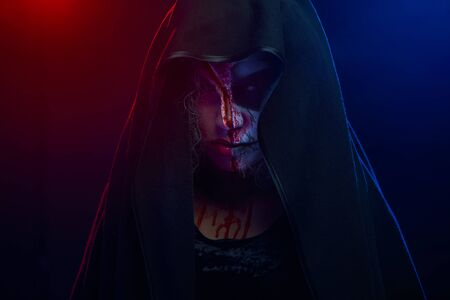 Portrait of horrible scary woman with painted skull face whose head covered with black mantle over background of red and blue lights. Concept of halloween face painting.