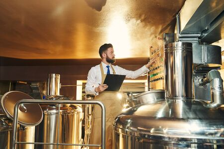 Handsome engineer of brewery inspecting process brewing beer. Worker in brown apron standing near equipment, storage tank, holding folder, looking at bulbs indicator lights.