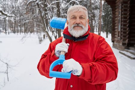 Portrait of bearded man looking at camera and smiling while removing snow in cold wintertime. Nice male worker in red jacket keeping shovel in hand and cleaning footpath in part. Concept of service.