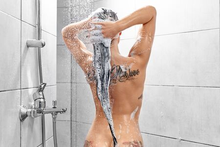 Naked sexy woman with tattoos on back in process of washing long hair in bathroom. Seductive woman with sporty body taking shower and caring about hair and skin. Concept of wellness and temptation.