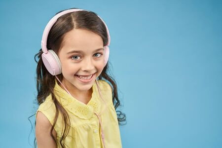 View from above of smiling girl in pink headphones looking at camera in studio. Pretty child listening music and relaxing. Positive female teen posing on blue isolated background. Concept of device. 版權商用圖片