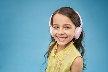 Funny girl wearing headphones listening music, looking at camera and smiling in studio. Happy child using earphones and enjoying songs. Pretty female teen posing on blue isolated background.