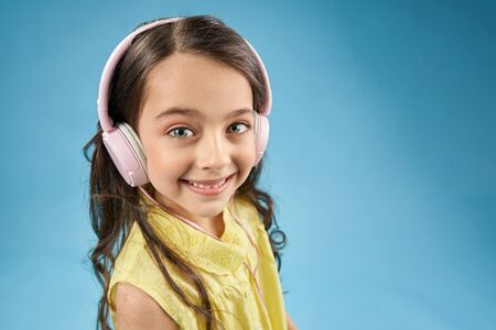 Positive child wearing pink earphones looking at camera and laughing on blue isolated background. Pretty little girl in yellow shirt listening music and enjoying modern device. Concept of technology.