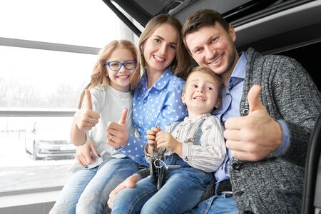 Happy family sitting in new comfortable car in auto salon, looking at camera, smiling and showing sign ok. Lovely parents with kids purchasing vehicle in showroom. Concept of automobile buying.