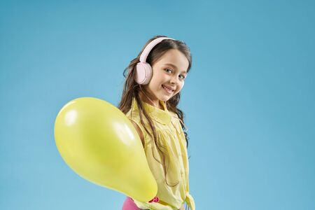 Happy little girl wearing headphones keeping yellow balloon and looking at camera in studio. Cheerful child playing and having fun. Positive model posing on blue isolated background.