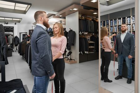 Attractive female tailor measuring length of sleeve of jacket in boutique. Young bearded male client trying on clothes, looking at mirror and choosing casual smart suit in shop. Concept of fitting.