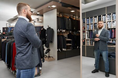 Serious male client looking at mirror, choosing and buying new casual smart suit in shop. Young businessman trying on fashionable jacket in boutique. Concept of style and male clothes.
