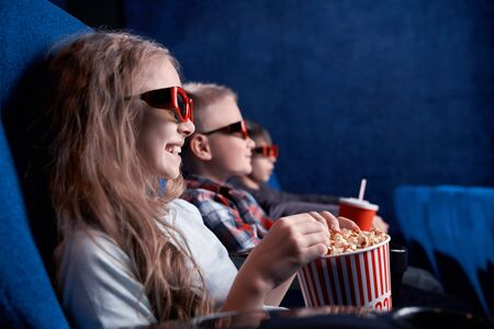 Side view of happy children wearing 3d glasses watching funny film in cinema. Excited friends eating popcorn, drinking aerated sweet water and having fun together. Concept of enjoyment and leisure.