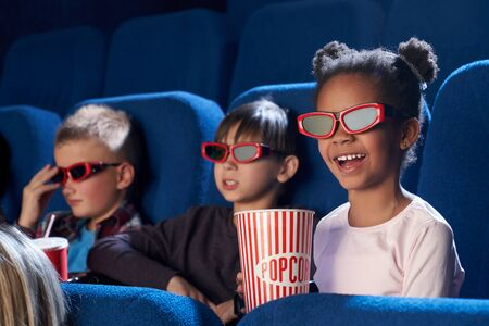 Happy child wearing 3d glasses, eating tasty popcorn and watching comical movie. Cute little girl spending free time with friends in cinema and laughing. Concept of leisure and entertainment. 스톡 콘텐츠