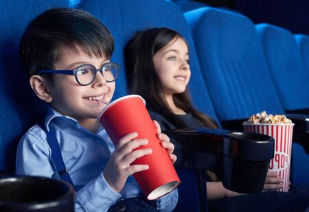 View from side of happy boy wearing glasses drinking aerated sweet water and watching interesting movie. Happy male child sitting with friend laughing and resting on weekends. Concept of leisure.