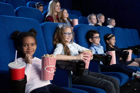 Lovely little girl sitting in cinema, looking at camera and smiling while watching movie. Small african girl eating popcorn and drinking aerated sweet water. Cocept of entertainment. Stock Photo