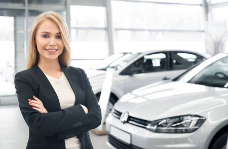 Smiling female car dealer with folded arms looking at camera and posing in front of new automobiles. Pretty woman wearing smart suit working in auto salon and selling cars to clients.