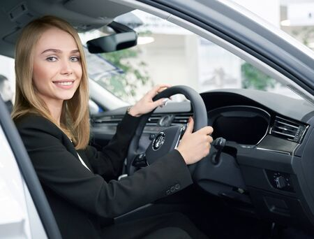 Young woman sitting in right handed automobile, looking at camera and smiling in auto showroom. Beautiful blonde chosing and testing new cars in auto salon. Concept of auto buying.