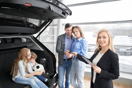 View from side of female car seller looking at camera and smiling while giving keys of car to new owners in auto salon. Car dealer selling new auto to happy family. Concept of auto purchasing.