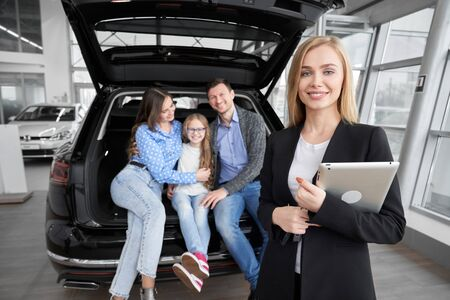 Front view of professional car dealer standing with tablet, looking at camera and posing while happy family testing auto on background. Female seller consulting and helping customers. 版權商用圖片