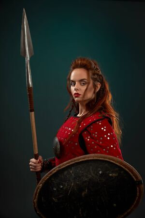 Side view of powerful female fighter in armor keeping spear and shield and posing on isolated background in studio. Young red haired woman looking at camera. Female hero fighting in combat. Reklamní fotografie