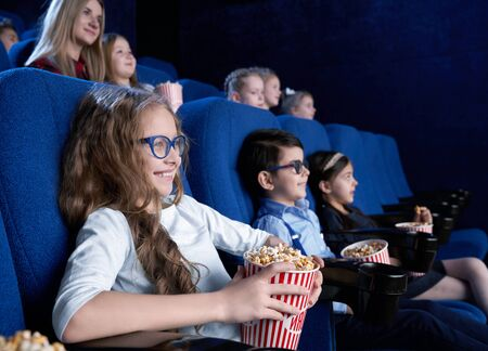 Cheerful girl in glasses eating popcorn and laughing in cinema. Long haired pretty girl sitting on comfortable blue seat, watching comical film and laughing. Concept of entertainment and fun.