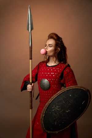 Female spartan warrior in red armor keeping shield and spear and chewing gum on isolated background in studio. Young strong woman looking forward and posing. Concept of power and positivity.