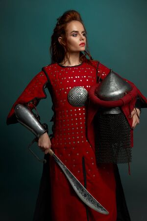 View form side of barbarian female fighter posing with helmet and knife in hands in studio. Young warrior at red armor looking aside on isolated background. Concept of confidence and weapon.