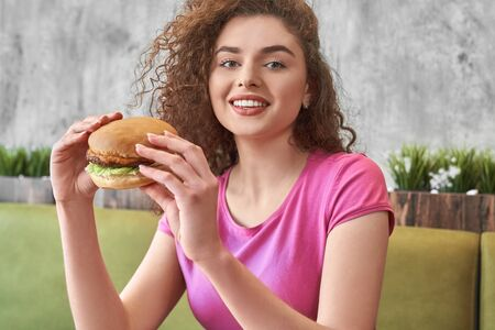 Front view of hungry pretty woman looking at camera while eating tasty big hamburger in cafe. Curly teenager smiling and posing while enjoying fast food in pizzeria. Concept of snack. 版權商用圖片