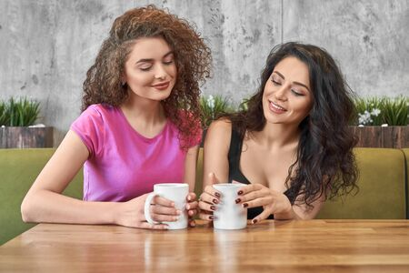 Best female friends drinking tea together, talking and enjoying free time in cafe. Attractive women having meeting and telling news to each other while waiting for order. Concept of friendship. Reklamní fotografie