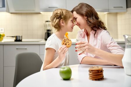 Side view pretty mother and little daughter eating cookies and drinking milk at kitchen. Female and girl sitting at table, looking at each other, laughing and touching with noses. Concept of love.