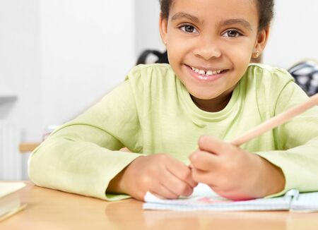 Selective focus of cute african girl looking at camera and laughing while learning at school. Pretty female student sitting at desk, keeping pen and drawing in copybook. Concept of studying.