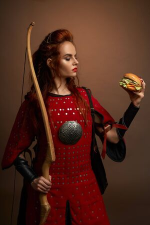 View from side of red haired female warrior with bow and arrow keeping tasty hamburger on isolated background in studio. Determined hunger female hero eating fast food. Concept of power.