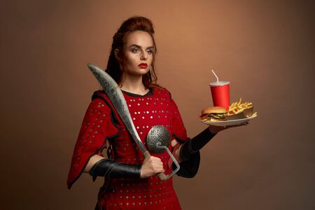 Beautiful female fighter in red armor keeping big knife and plate with fast food in studio. Determined woman looking aside and posing with hamburger and free potato. Concept of food of heroes.
