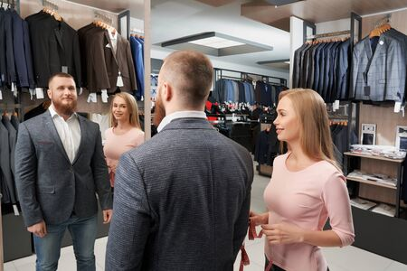 Confident businessman choosing new casual jacket in shop. Young male client looking at mirror while pretty female assistant helping and servicing him. Concept of clothes and fitting. 免版税图像