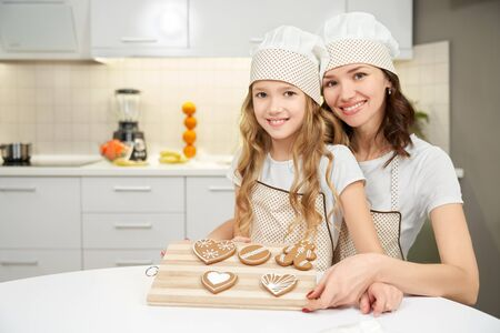 Front view of beautiful woman with little daughter in cooking hats and aprons looking at camera and keeping tray with cookies. Mother and little girl baking together at home. Concept of culinary. Stockfoto