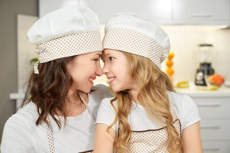 Side view of attractive mother and little daughter wearing cooking hats and aprons looking at each other, hugging and touching with noses. Lovely family cooking together at kinchen. Concept of love.