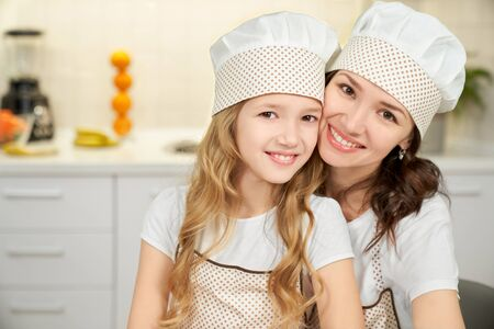 Portrait of little daughter and mother in aprons and hats looking at camera and smiling while cooking together at kitchen. Cute girl helping mother and baking cookies. Concept of culinary and love.