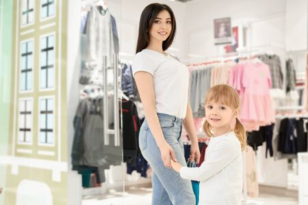 Beautiful, stylish brunette and cute little girl shopping in modern shopping centre. Mother and daughter posing, smiling, looking at camera and holding hands in store with clothing for children.