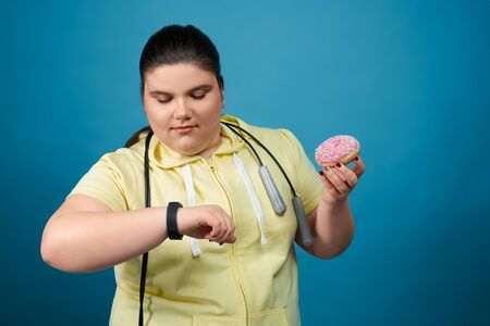 Plump brunette young girl keeping donut on her hand, watching on her watch on another hand. Fat female is trying not to eat unhealthy food and begin to do sport with rope hanging around her neck Stock Photo