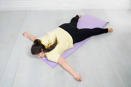 Woman with curvy body in yellow hoodie and black legging is lying on violet mat in star pose after training indoors. Young brunette girl having rest after intensive workout.
