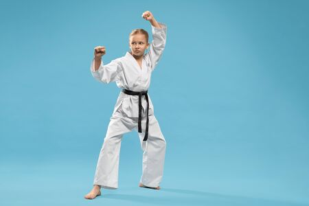 Confident junior in kimono with black belt practising karate and jujitsu. Serious karate girl standing in stance and punching with hand on blue background.