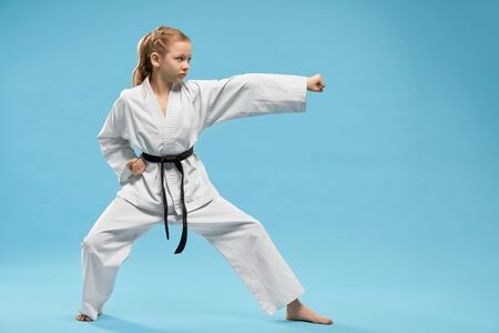 Pretty, young girl practicing karate and jujitsu. Confident junior wearing in white kimono with black belt standing in stance. Concept of wellness and martial arts. 版權商用圖片