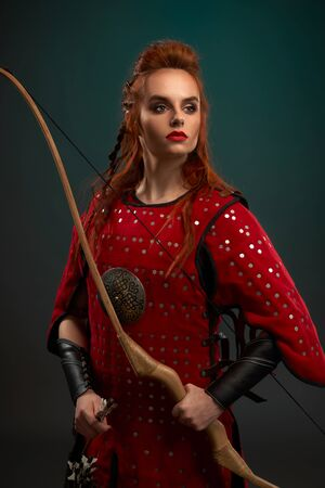 Portrait of attractive female warrior wearing red armor keeping bow and looking aside on isolated background in studio. Young red haired strong woman posing. Concept of weapon and confidence. Reklamní fotografie