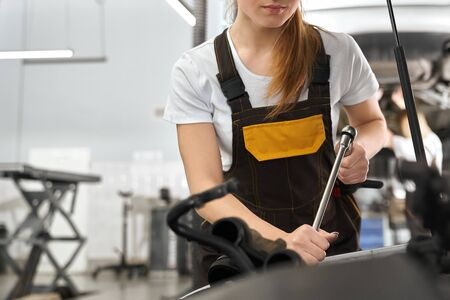 Selective focus of pretty woman working in auto service. Professional female mechanic in white shirt and coverall keeping wrench and fixing damage in automobile. Concept of maintenance.