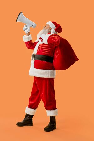 Authentic Santa Claus with red bag full of presents shouting in white megaphone in studio. Happy aged christmas character in traditional costume announcing about holidays